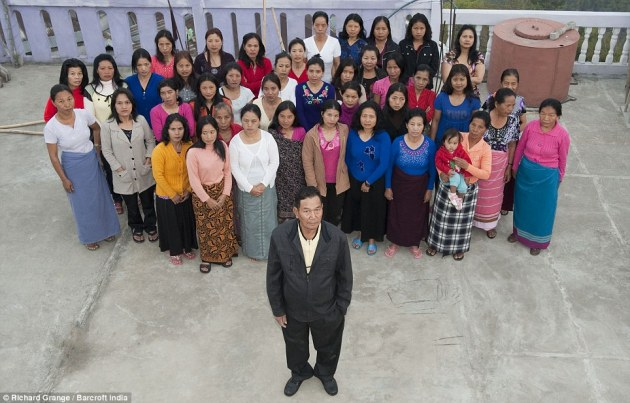 Mr Ziona Chana poses with his 39 wives at their home in Baktawang, Mizoram, India